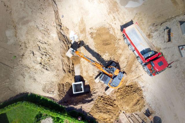 Photographie vue drone d'un suivi de chantier pendant les travaux avec un camion et une pelleteuse