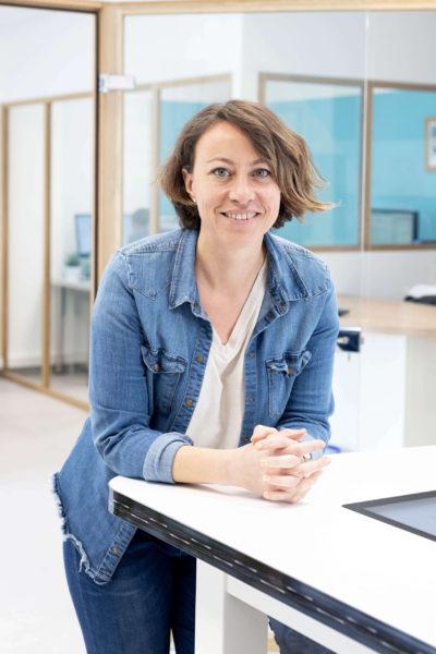 Photo portrait corporate d'une femme en intérieur sur son lieu de travail